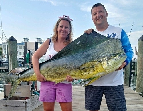 Kristy Frashure poses with her husband, Ryan, and the record-setting common dolphinfish she caught off Ocean City on Aug. 16, 2019. (Maryland Department of Natural Resources)