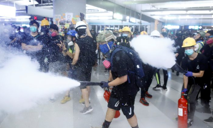 Protesters fire nitrogen extinguishers during a stand off at Yuen Long MTR station, the scene of an attack by suspected triad gang members a month ago, in Yuen Long, New Territories, Hong Kong, China on Aug. 21, 2019. (Thomas Peter/Reuters)