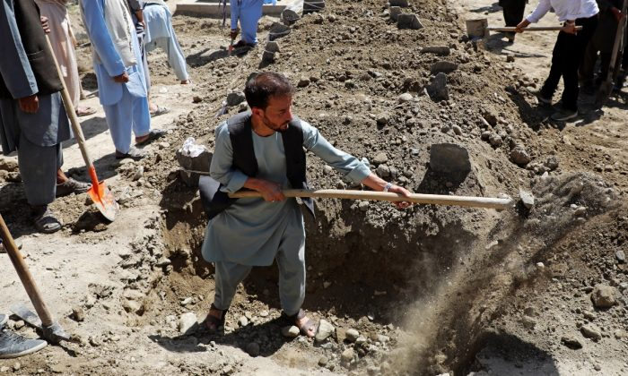 Afghan men dig a grave during a mass funeral following a wedding suicide bombing in Kabul, Afghanistan on Aug. 18, 2019. (Omar Sobhani/Reuters)