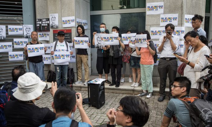 People hold a portrait of British consulate worker Simon Cheng, during a gathering to petition the British government to assist in his release, outside the British Consulate in Hong Kong on Aug. 21, 2019. (Chris McGrath/Getty Images)