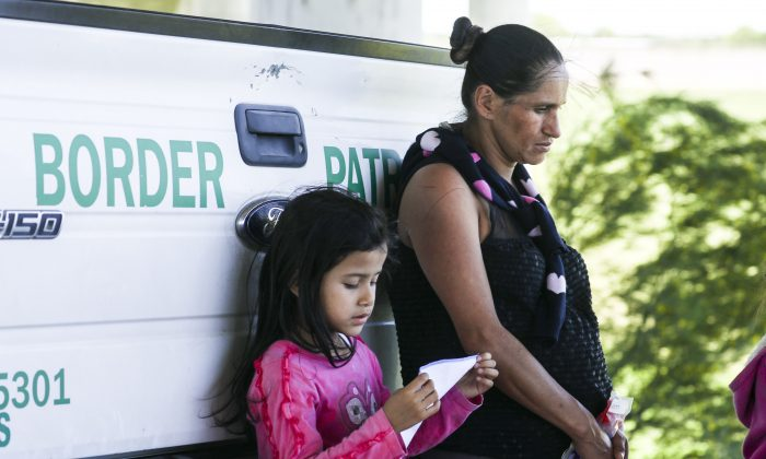 A heavily pregnant woman and a girl lean against a Border Patrol truck after being apprehended for illegally crossing the U.S. border over the Rio Grande from Mexico near McAllen, Texas, on April 18, 2019. (Charlotte Cuthbertson/The Epoch Times)