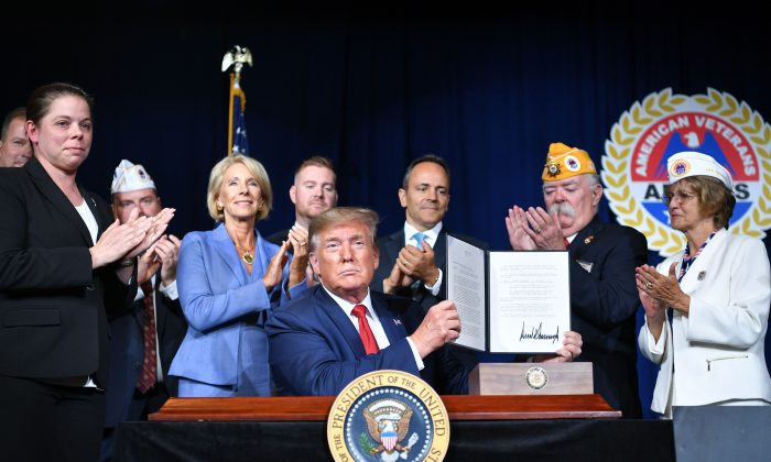 President Donald Trump sign a Presidential Memorandum on Discharging the Federal Student Loan Debt of Totally and Permanently Disabled Veterans, at the American Veterans 75th National Convention in Louisville, Kentucky, on Aug. 21, 2019. (MANDEL NGAN/AFP/Getty Images)
