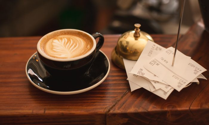 Stock photo of a cup of coffee and some receipts at a restaurant. (Carli Jeen/Unsplash)