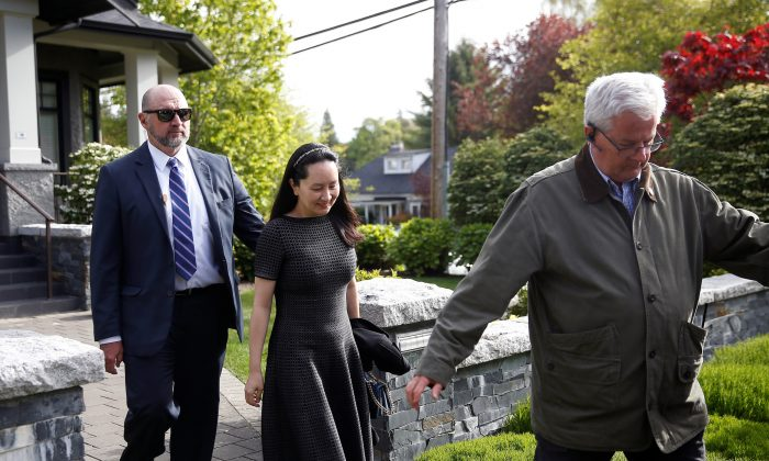 Huawei's Financial Chief Meng Wanzhou leaves her family home flanked by private security in Vancouver, British Columbia, Canada on May 8, 2019. (Lindsey Wasson/Reuters)