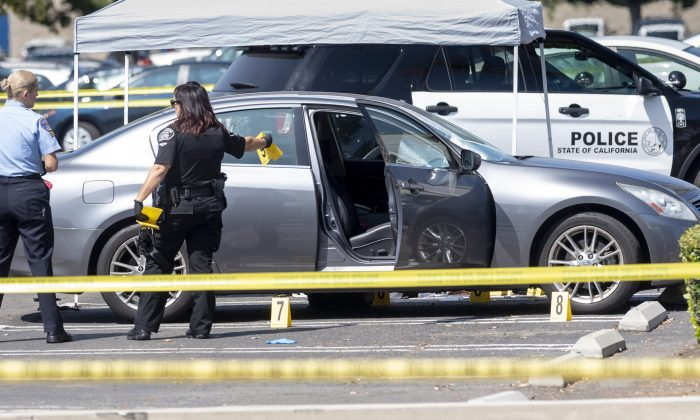 Police investigate a car where a retired Cal State Fullerton administrator was stabbed to death in Fullerton, Calif. on August 19, 2019. (Paul Bersebach/The Orange County Register via AP)