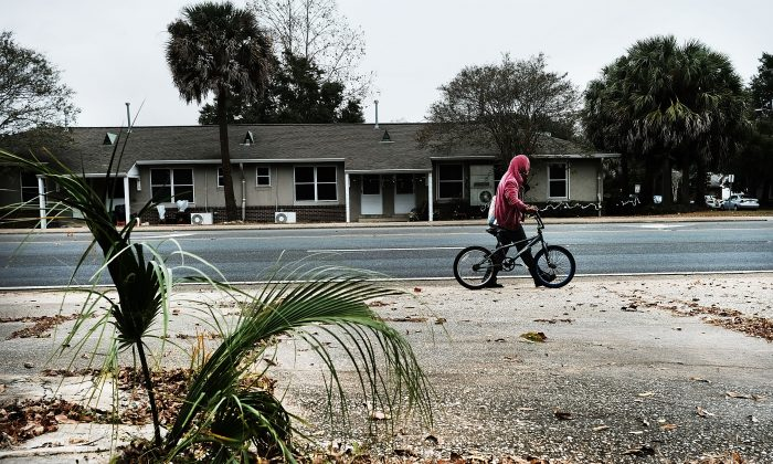 A man walks his bicycle in a struggling neighborhood in Pensacola, Fla., on Dec. 4, 2016. (Spencer Platt/Getty Images)