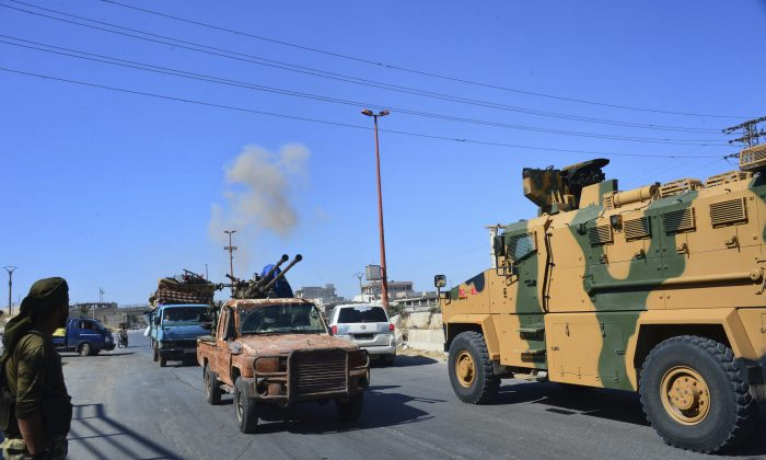 Fighters with the Free Syrian army drive their pick-up truck (L), past a Turkey Armed Forces convoy, at a highway between Maaret al-Numan and Khan Sheikhoun in Idlib province, Syria, on Aug. 19, 2019. Murat Kibritoglu/DHA via AP