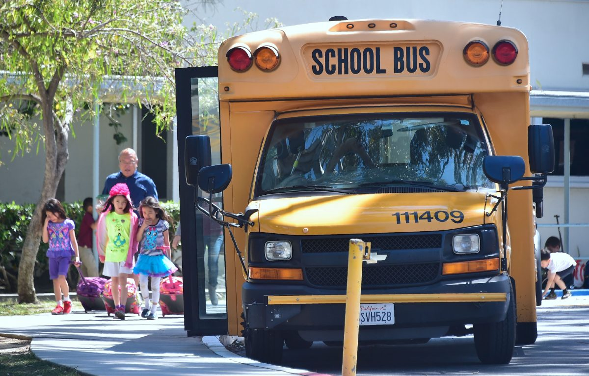 Children walk past a School Bus