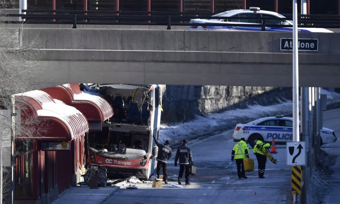 Officials from Transport Canada look at the scene where a double-decker city bus struck a transit shelter at the start of the afternoon rush hour at Westboro Station in Ottawa, on Saturday, Jan. 12, 2019. (Justin Tang/The Canadian Press)