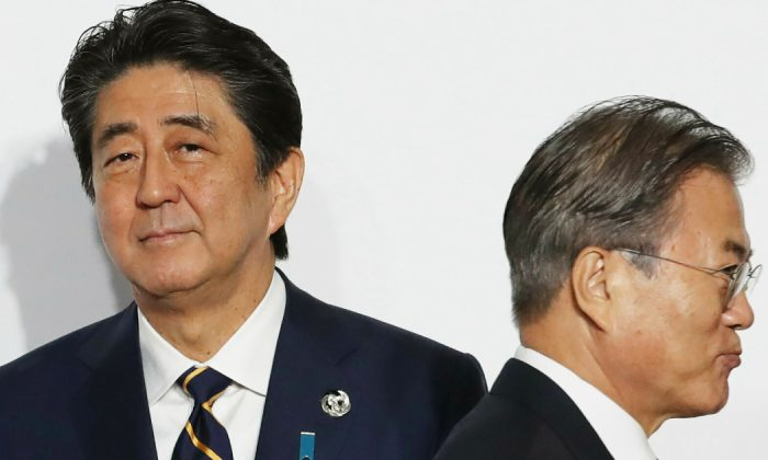 South Korean President Moon Jae-in, right, walks by Japanese Prime Minister Shinzo Abe upon his arrival for a welcome and family photo session at the G-20 leaders summit in Osaka, western Japan. (Kim Kyung-Hoon/Pool Photo via AP, File)