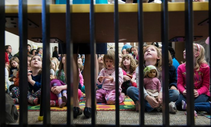 Children listen to a speaker at a library in Arlington, Virginia, on April 4, 2013. (BRENDAN SMIALOWSKI/AFP/Getty Images)