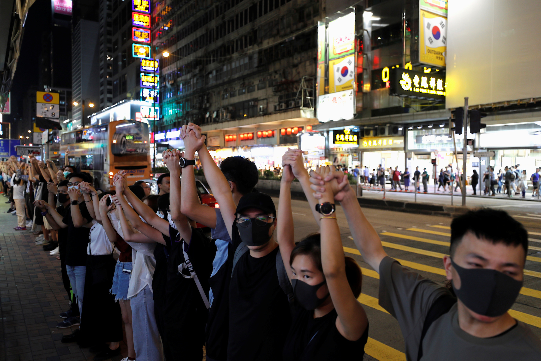 Anti-extradition bill protesters hold hands to form a human chain during a rally to call for political reforms at Mongkok, in Hong Kong