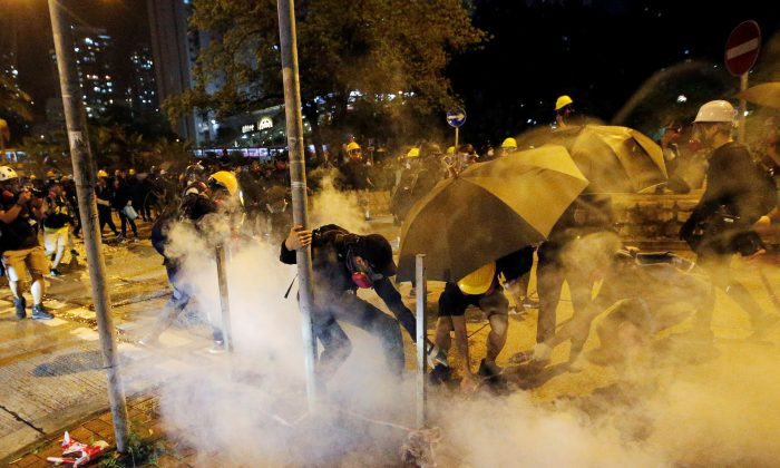 Anti-extradition bill protesters extinguish a tear gas cartridge during clashes with police near Wong Tai Sin station in Hong Kong, on Aug. 24, 2019. (Willy Kurniawan/Reuters)