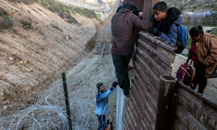 Central American migrants cross the U.S.-Mexico border fence from Tijuana, Mexico to San Diego County, Calif. on Dec. 27, 2018. (GUILLERMO ARIAS/AFP/Getty Images)