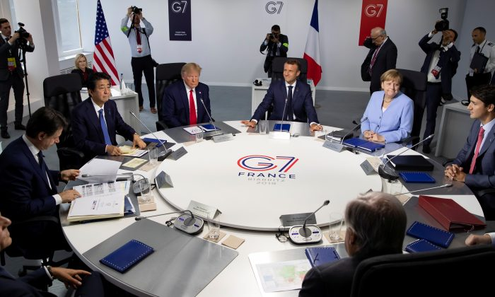 (L-R) EU Council President Donald Tusk,  Italian Prime Minister Giuseppe Conte, Japanese Prime Minister Shinzo Abe, U.S. President Donald Trump, French President Emmanuel Macron, German Chancellor Angela Merkel, Canadian Prime Minister Justin Trudeau attend a work session during the G7 summit in Biarritz, France on Aug. 26, 2019. (Ian Langsdon/Pool via Reuters)