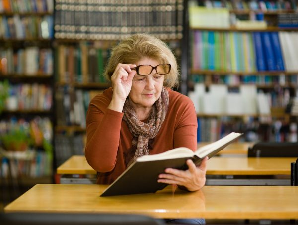 An elderly woman with glasses reads a book