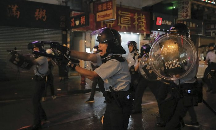 Policemen pull out their guns after a confrontation with demonstrators during a protest in Hong Kong, on Aug. 25, 2019. (AP Photo/Vincent Yu)