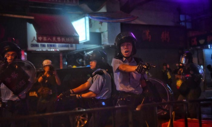 Police officers point their guns at protesters in Tseun Wan in Hong Kong on Aug. 25, 2019. (Lillian  Suwanrumpha/AFP/Getty Images)