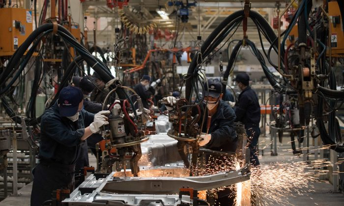 Workers weld SUV parts at the BAIC (Beijing Automotive Group Co) SUV assembly line in Beijing on August 29, 2018. NICOLAS ASFOURI/AFP/Getty Images