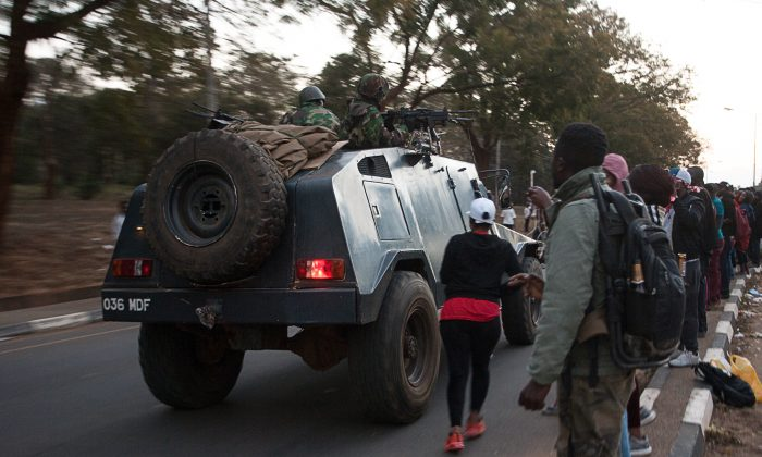 Protesters watch a Malawi Defense Force armored vehicle passing by during an overnight vigil against the result of the May 21 presidential vote in Lilongwe, Malawi, on July 4, 2019. (Amos Gumulira/AFP/Getty Images)