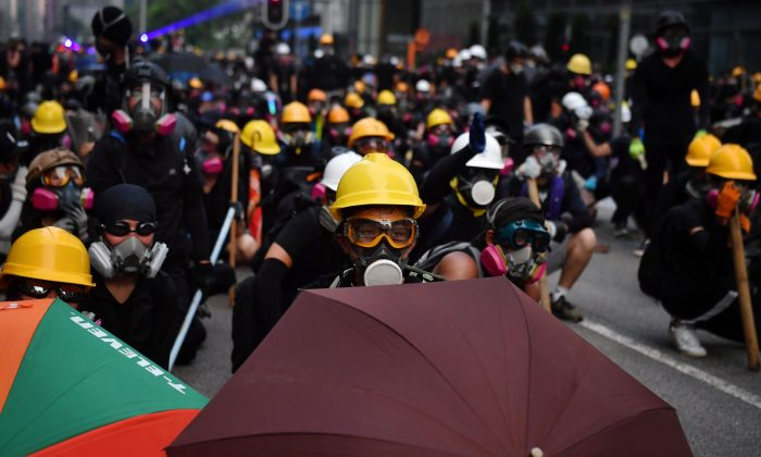 Protesters with umbrellas and protective gear face off with riot police at Kowloon Bay in Hong Kong on August 24, 2019. LILLIAN SUWANRUMPHA/AFP/Getty Images