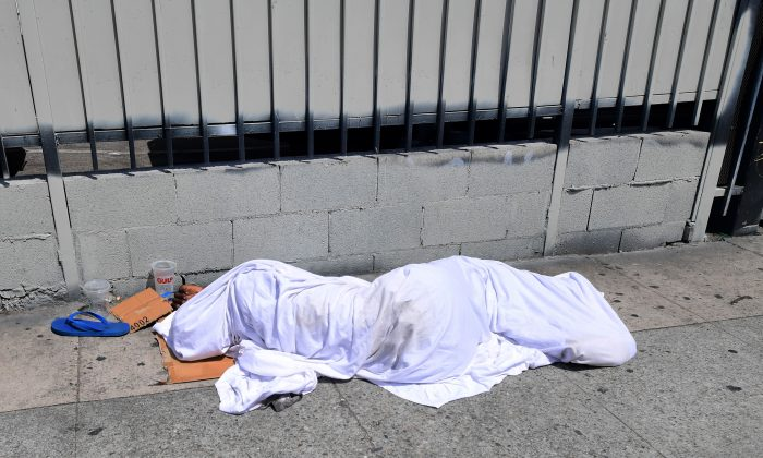 A homeless person sleeping under sheets along a sidewalk in Los Angeles on Aug. 22, 2019. (Frederic J. Brown/AFP/Getty Images)