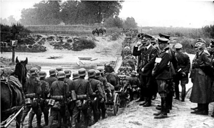 Hitler watching German soldiers marching into Poland in September 1939, shortly after the signing of the Molotov-Ribbentrop Pact, a German-Soviet non-aggression pact. (Bundesarchiv, Bild 183-S55480/CC-BY-SA 3.0)
