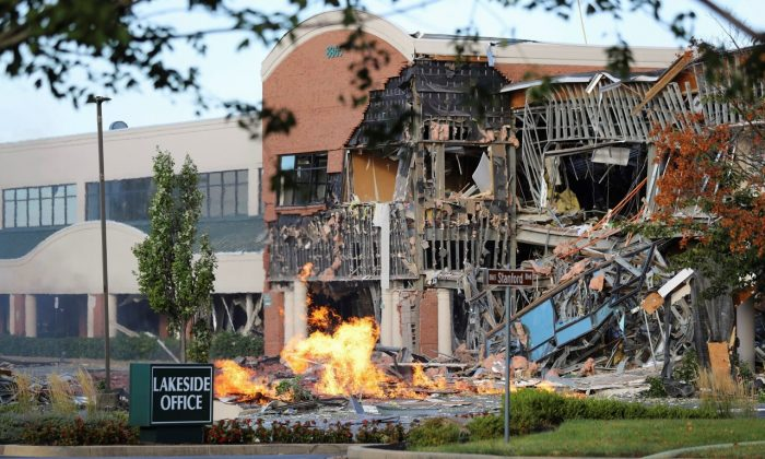 A damaged building and burning debris nearby after an explosion at an office complex and shopping center in Columbia, Md., on Aug. 25, 2019. (Howard County Fire And Rescue via AP)