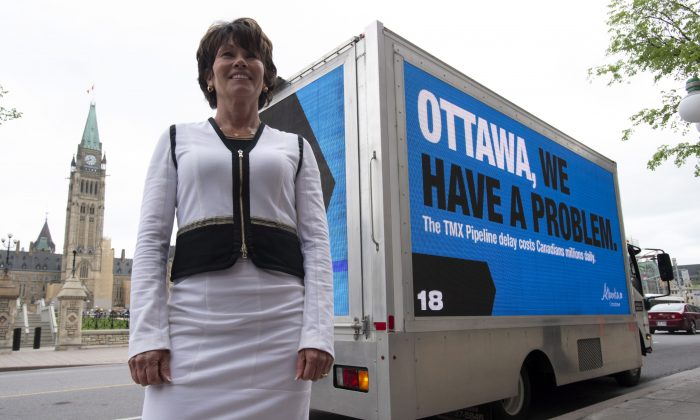 Alberta Energy Minister Sonya Savage stands in front of a billboard vehicle showing a campaign the Alberta government is undertaking in Ottawa on May 29, 2019. (The Canadian Press/Adrian Wyld)