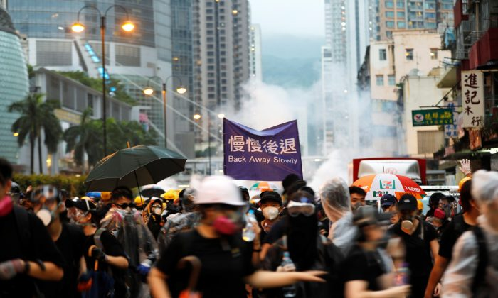 Anti-extradition bill protesters run as riot police fire tear gas during a protest in Hong Kong, China on Aug. 25, 2019. (Willy Kurniawan/Reuters)
