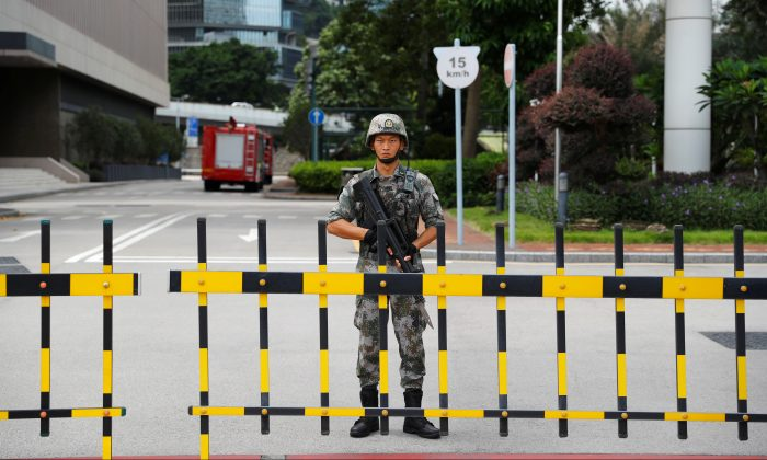 A Chinese People's Liberation Army (PLA) soldier guards the entrance to the PLA Hong Kong Garrison headquarters in the Central Business District in Hong Kong on Aug. 29, 2019. (Anushree Fadnavis/Reuters)