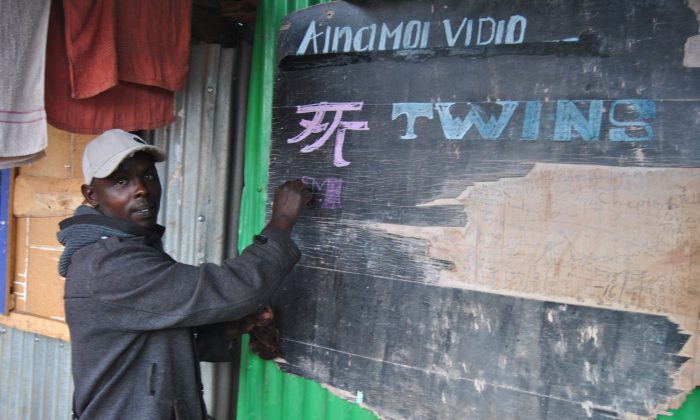 Leonard Biegon writes the name of the current Chinese movie showing at his video store at the Ainamoi shopping center, Kenya, on Aug. 24, 2019. (Dominic Kirui for The Epoch Times)