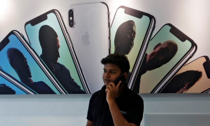 A salesperson speaks on the phone at an Apple reseller store in Mumbai, India on July 27, 2018. (Francis Mascarenhas/Reuters)