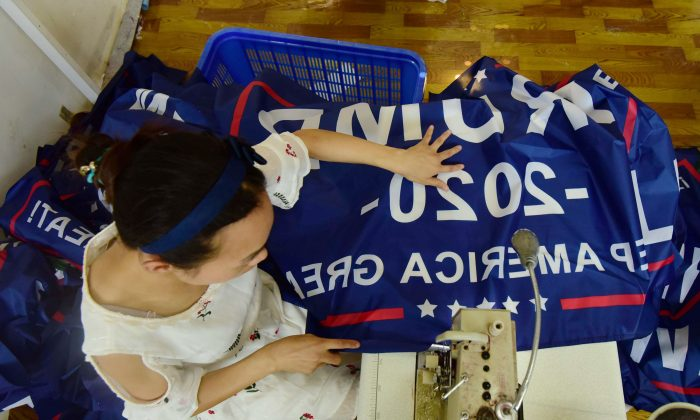 """A Chinese worker sews a banner declaring President Donald Trump's re-election intentions that reads """"Trump 2020: Keep America Great"""" at a factory in Fuyang, Anhui Province, China on July 13, 2018. (AFP/Getty Images)"""