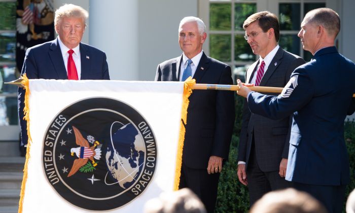A member of the US military unfurls the new US Space Command flag alongside President Donald Trump (L), Vice President Mike Pence (2nd L) and Secretary of Defense Mark Esper during an event establishing the US Space Command in the Rose Garden of the White House on Aug. 29, 2019. (Saul Loeb/AFP/Getty Images)