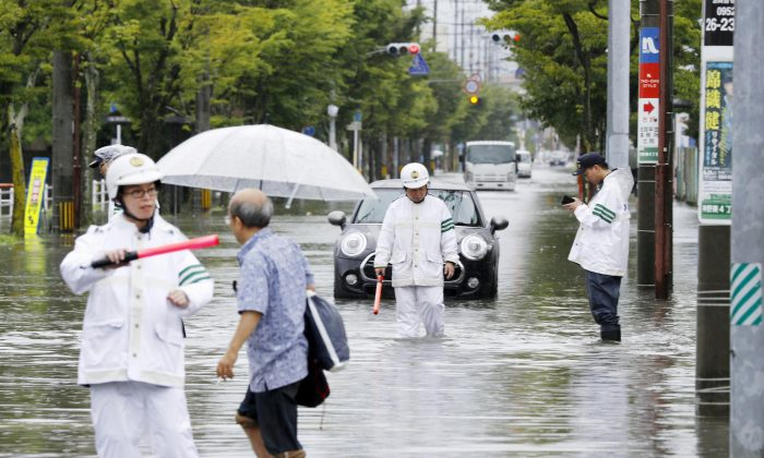 Police officers check a submerged street at a flooded area in Saga, Saga prefecture, southern Japan August 28, 2019. (Kyodo/via Reuters)
