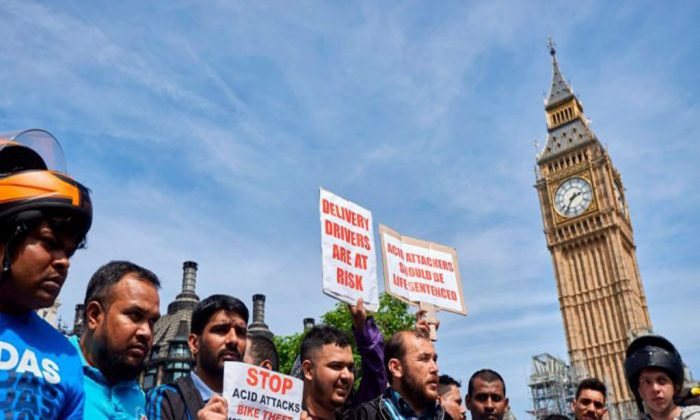 Following a spate of acid attacks on July 13, motorcycle delivery drivers and motorcyclists take part in a demonstration in Parliament Square, on July 18, 2017.