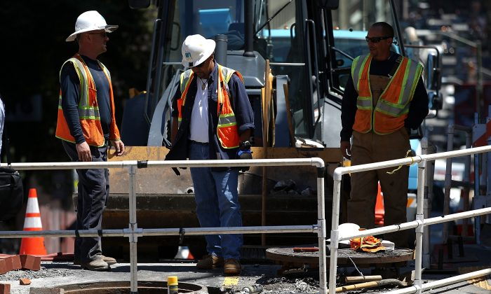 Pacific Gas and Electric (PG&E) workers look into a hole at a job site in San Francisco, Calif., on July 30, 2014. (Justin Sullivan/Getty Images)