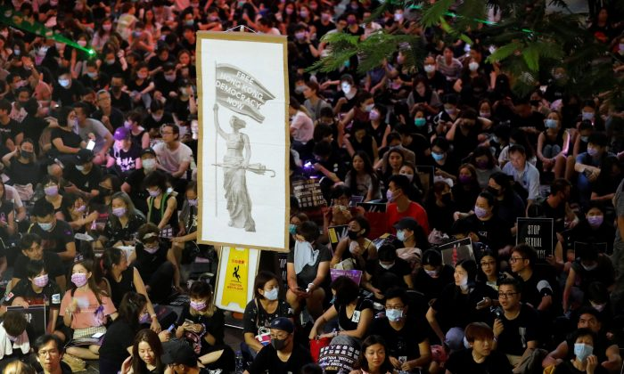 Protesters carry placards as they gather to condemn alleged sexual harassment of a detained demonstrator at a police station, in Hong Kong, China on Aug. 28, 2019. (Anushree Fadnavis/Reuters)