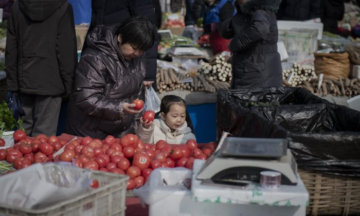 A young girl helps a woman to choose tomatoes at a market in Beijing on Feb. 27, 2019. (Nicolas Asfouri/ AFP/Getty Images)