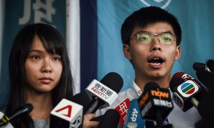 Pro-democracy activists Agnes Chow (L) and Joshua Wong (R) speak to the press after they were released on bail at the Eastern Magistrates Courts in Hong Kong on Aug. 30, 2019. (Lillian Suwanrumpha/AFP/Getty Images)