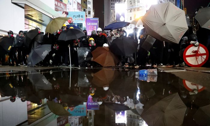 Demonstrators take cover during a protest in Hong Kong, on August 31, 2019. (REUTERS/Kai Pfaffenbach)