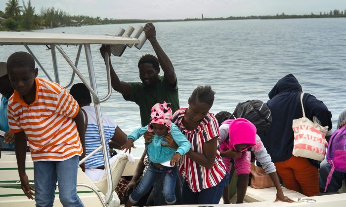 A woman carries a girl in her arms after being evacuated from a nearby Cay due to the danger of floods after arrive on a ship at the port before the arrival of Hurricane Dorian in Sweeting's Cay, Grand Bahama, Bahamas, on Aug. 31, 2019.   (Ramon Espinosa/AP Photo)