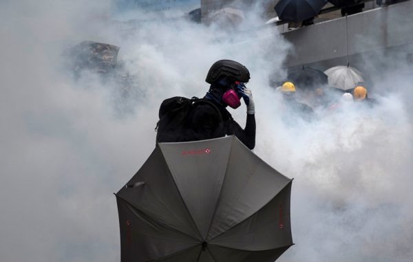 A demonstrator reacts after police fires tear gas during a protest in Hong Kong