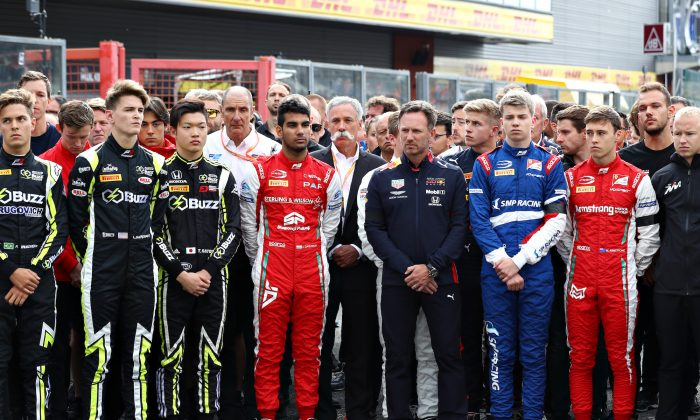 Members of the Formula 1, Formula 2, and Formula 3 communities observe a minute of silence in tribute to Anthoine Hubert at Circuit de Spa-Francorchamps in Spa, Belgium, on Sept. 1, 2019. (Mark Thompson/Getty Images)