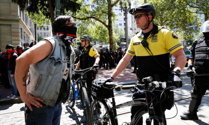 "An unidentified protester clashes with a police officer during a demonstration between the left and right at Pioneer Courthouse Square, in Portland on June 29, 2019. These clashes led an ex-marine to stand outside Mayor's office on July 20 and warn about ""slaughtering"" Antifa that led FBI to confiscate his guns. (Moriah Ratner/Getty Images)"