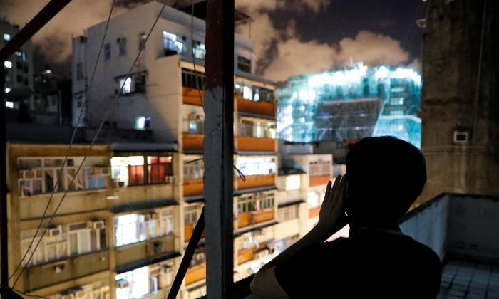 Choco Chu, 23, shouts slogan from his rooftop at Sham Shui Po in Hong Kong, China on Aug. 29, 2019. (Tyrone Siu/Reuters)