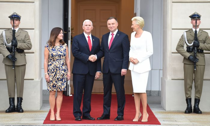 Polish President Andrzej Duda (2nd R) and US Vice President Mike Pence (2nd L) shake hands as their wives Agata Kornhauser-Duda (R) and Karen Pence (L) look on at the presidential palace in Warsaw on Sept. 2, 2019. (JANEK SKARZYNSKI/AFP/Getty Images)