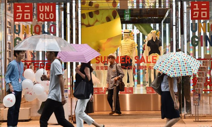 Pedestrians walk in front of a shop of Japan's Uniqlo-operator Fast Retailing in Tokyo on July 15, 2016. (Kazuhiro Nogi/AFP/Getty Images)