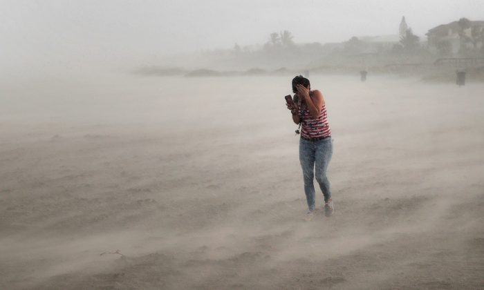 A woman seeks cover from wind, blowing sand and rain whipped up by Hurricane Dorian as she walks on the beach in Cocoa Beach, Florida, on Sept. 2, 2019. (Scott Olson/Getty Images)